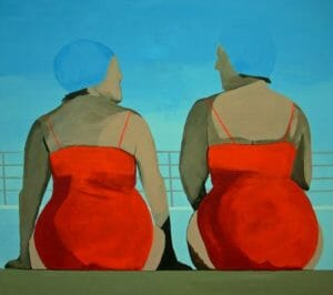 two women in bathers with their backs to us sitting on the edge of a swimming pool
