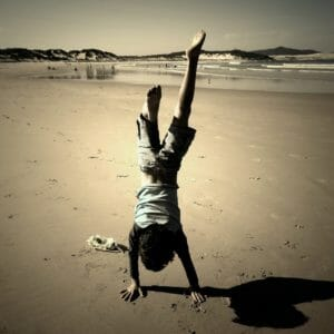 Young boy doing handstand on the beach.