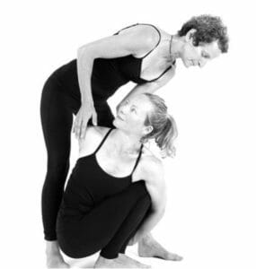 A yoga teacher adjusting her student in a twist pose
