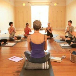 Yoga practice class with students and teacher seated