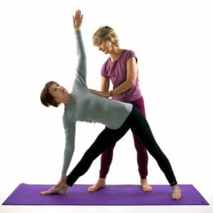Photo of a yoga adjustment, Eve assisting Jane in triangle yoga pose.