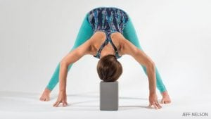 woman doing yoga standing pose bending forward.