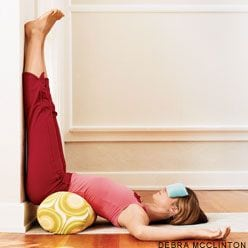 A woman lying in legs up the wall yoga pose, on a bolster.