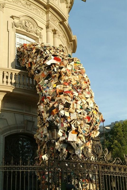 Photo of street art, a huge pile of books falling out of a first floor building window