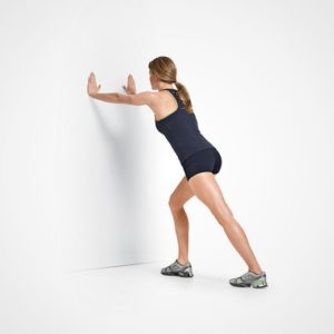 Woman doing yoga pose for knee pain , hands on the wall, front leg bent into a lunge.
