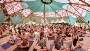 Photo of crowd of yoga students meditating in a tent.