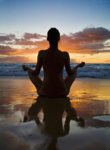 Meditator seated at the beach at sunrise.