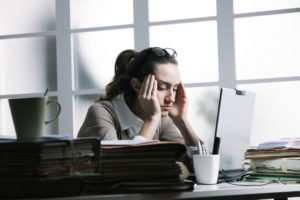 A woman sitting at her desk, stressed out, head in hands, eyes closed.